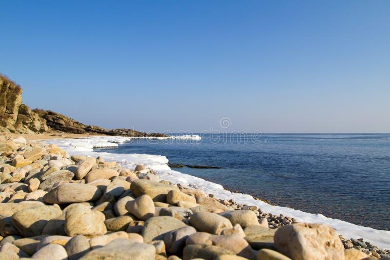 Pierres de mer sur la plage, glace d'hiver images stock