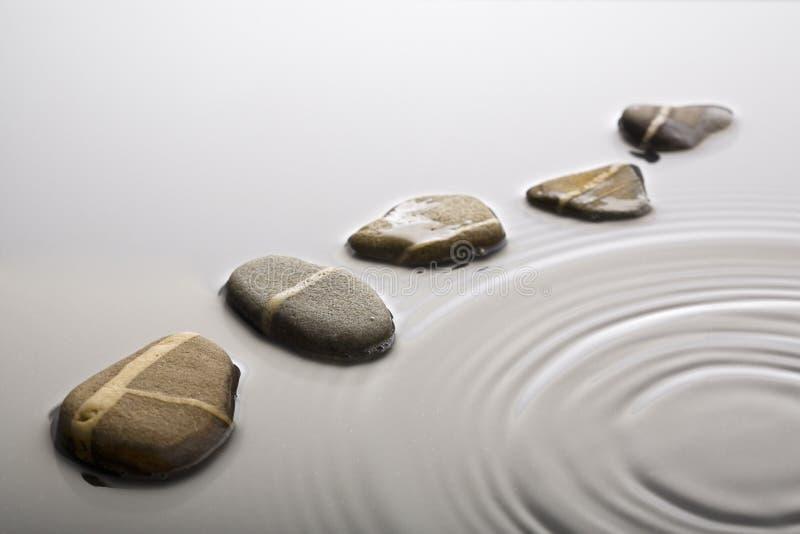 Pierres de progression dans l'eau ondulée photos stock