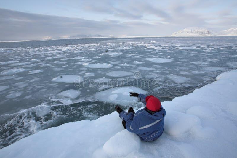 Pierres de projection d'un homme dans la mer arctique photos stock
