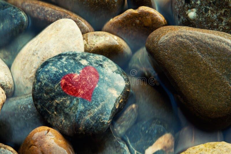 Pierres en rivière avec le symbole peint de coeur photos libres de droits