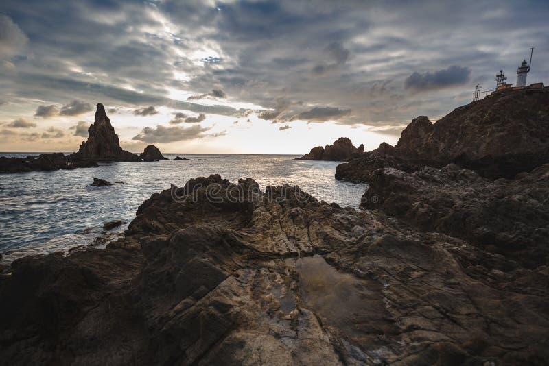 Pierres et roches sur Cabo De Gata, Almeria, Espagne avec le phare image stock
