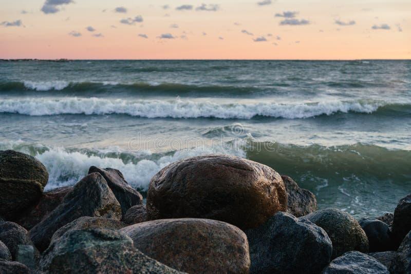 Pierres humides contre les vagues de mer et le ciel de lever de soleil photos stock