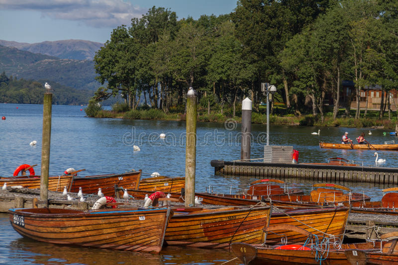 Piers and boats on edge of Bowness-on-Windermere in Lake District in Cumbria, United Kingdom. Bowness-on-Windermere, United Kingdom - September 7, 2015: Photo of royalty free stock images