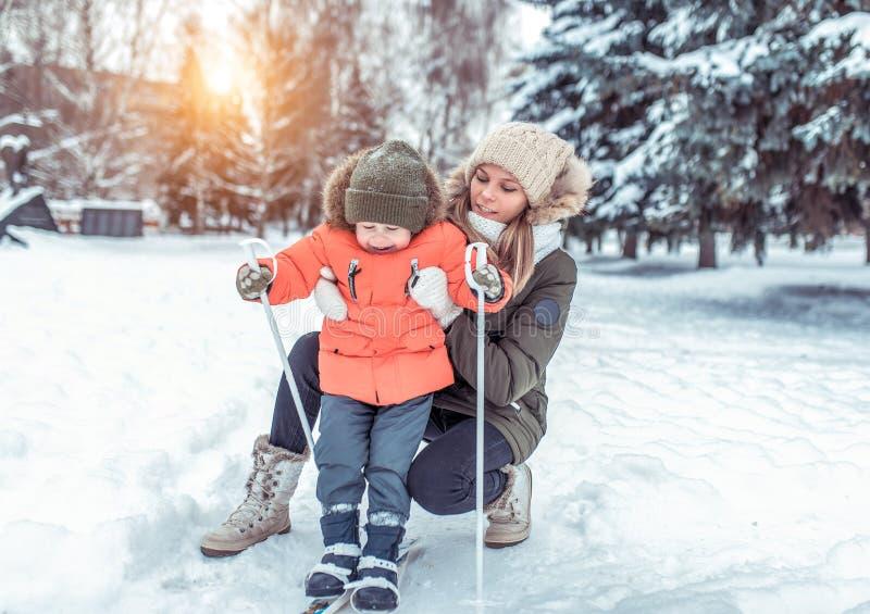 Pierwsi kroki chłopiec dziecko na dziecka narciarstwie z kijami Bawić się zabawy przejażdżkę i w parku w zimie Mam utrzymania fotografia royalty free
