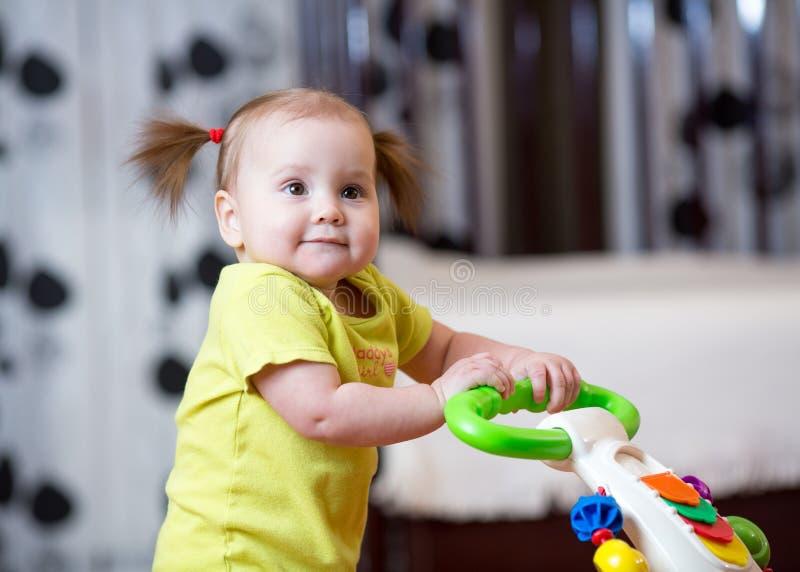 Pierwsi kroki małe dziecko dziewczyna w dziecko piechurze fotografia royalty free
