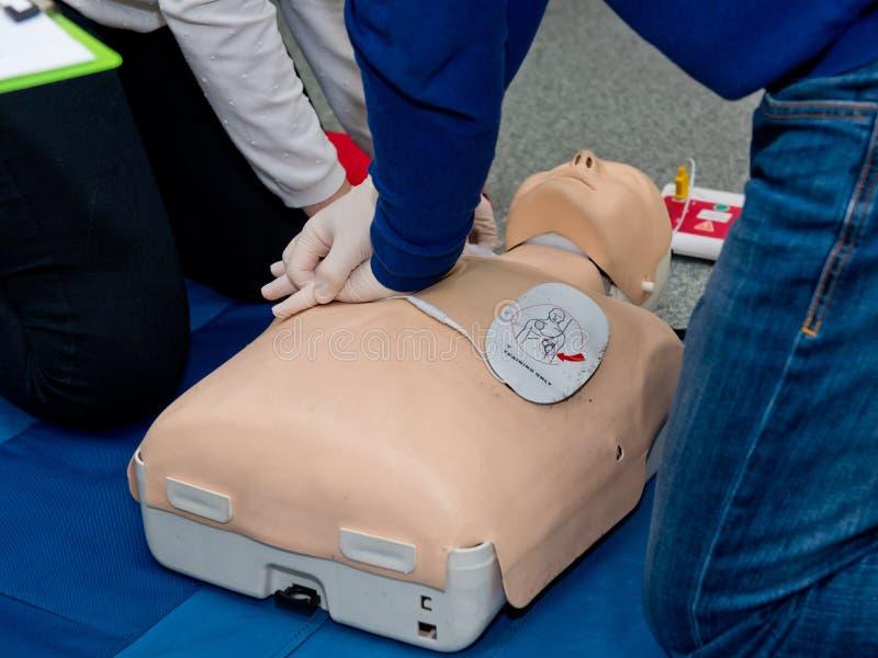 Pierwszej pomocy cardiopulmonary resuscitation kurs używać automatyzującego zewnętrznie defibrillator zdjęcia stock