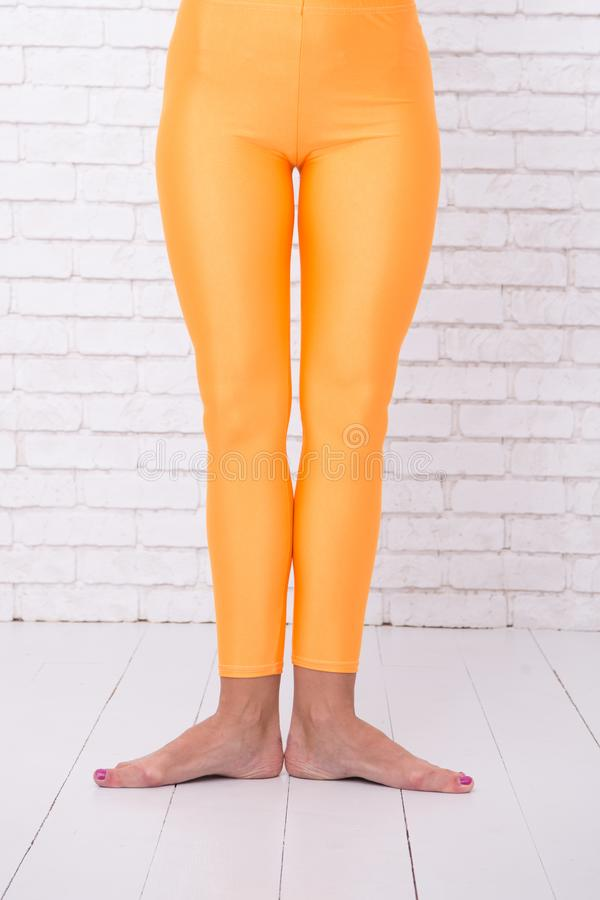 Pierwszy baletnicza pozycja żeńscy cieki w pomarańczowych rajstopy noga tancerz w pierwszy pozyci taniec klasa dla beginner balet fotografia royalty free