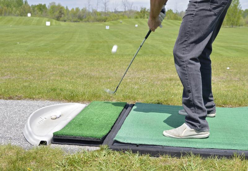 Pierwszy plan - golfista uderza tr?jnika strza? przy practive pasmem zdjęcia royalty free