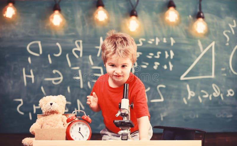 Pierwszy poprzedni zainteresowany w studiowaniu, uczenie, edukacja Żartuje chłopiec blisko mikroskopu w sala lekcyjnej, chalkboar zdjęcie royalty free