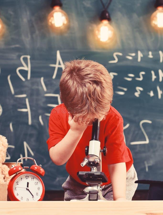 Pierwszy poprzedni zainteresowany w studiowaniu, uczenie, edukacja Dzieciak chłopiec spojrzenia w mikroskop w sala lekcyjnej, cha zdjęcia stock