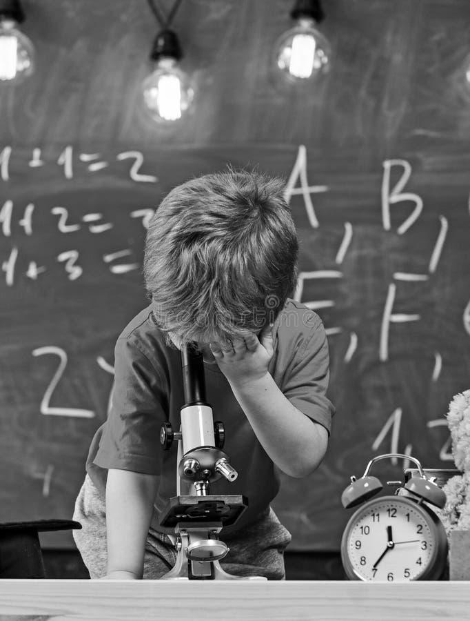 Pierwszy poprzedni zainteresowany w studiowaniu, uczenie, edukacja Dzieciak chłopiec spojrzenia w mikroskop w sala lekcyjnej, cha obrazy stock
