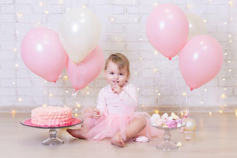 Pierwszy urodziny - śliczny małej dziewczynki łasowania tort nad ściana z cegieł półdupkami zdjęcia stock