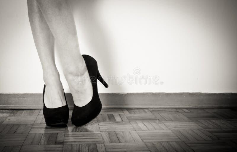 Pies atractivos jovenes de la mujer con los tacones altos y las piernas negros, cierre para arriba foto de archivo