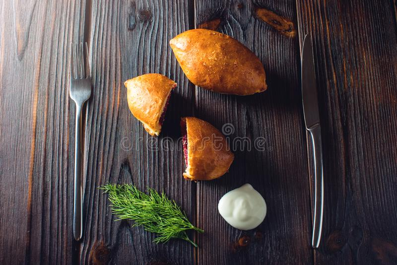 Pies with cabbage, potatoes, meat, berries garnished with sour cream. Traditional Russian food. Pies with cabbage, potatoes, meat, cherries, berries garnished royalty free stock image