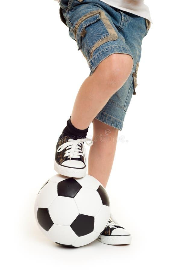 Pies calzados en zapatillas de deporte y balón de fútbol foto de archivo