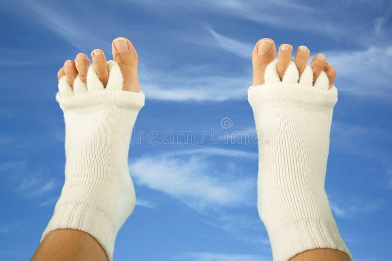 Pies con los calcetines del separador del dedo del pie en fondo del cielo fotos de archivo