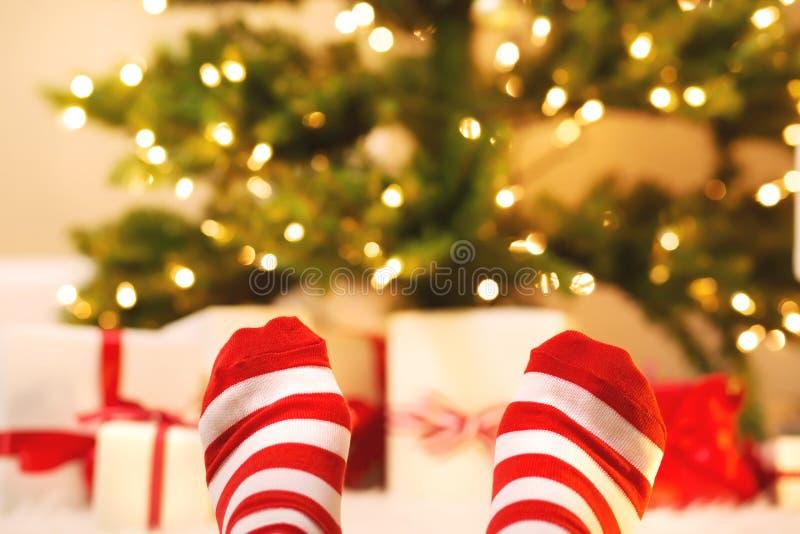 Pies con los calcetines rayados con las cajas de regalo de la Navidad foto de archivo libre de regalías
