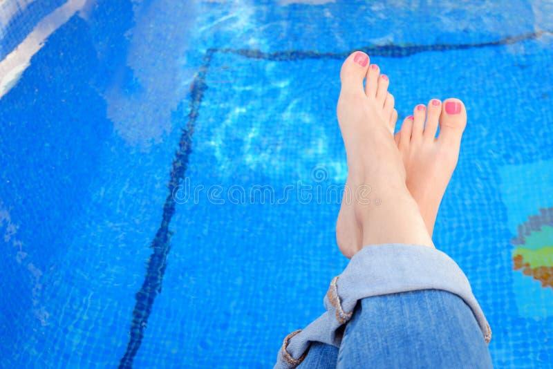 Pies cruzados de la mujer en tejanos por la piscina foto de archivo libre de regalías