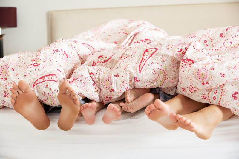 Pies de la familia que empujan hacia fuera del Duvet en cama foto de archivo libre de regalías