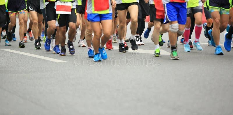 Pies de la gente en el camino de ciudad en raza corriente del maratón imágenes de archivo libres de regalías