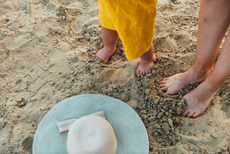Pies de la madre y del bebé en la arena de la playa con el sombrero Viaje del verano con el niño Tomar el sol concepto imágenes de archivo libres de regalías