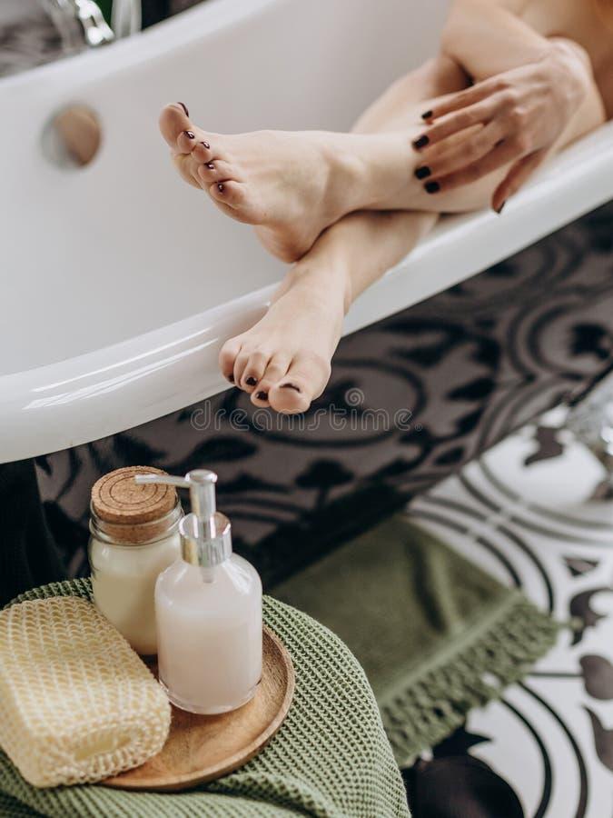 Pies de la muchacha del cuarto de baño de la dulzura de cosméticos del tulipán conceptuales fotos de archivo