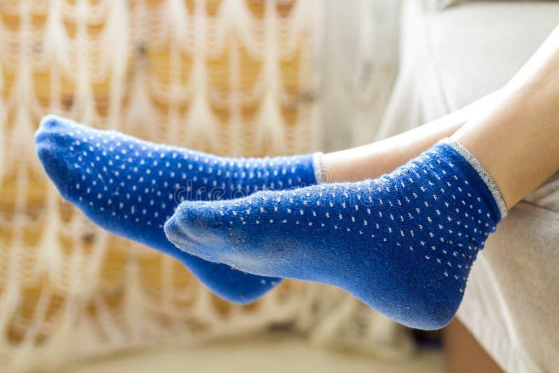 Pies de la mujer en calcetines azules Concepto del día de fiesta de la relajación y de la comodidad foto de archivo