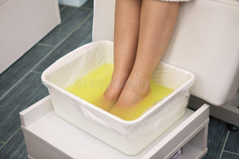 Pies de la mujer en cuenco del balneario con agua amarilla imagen de archivo