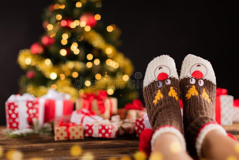 Pies de la mujer en los calcetines de lana, fondo de la Navidad de la falta de definición foto de archivo