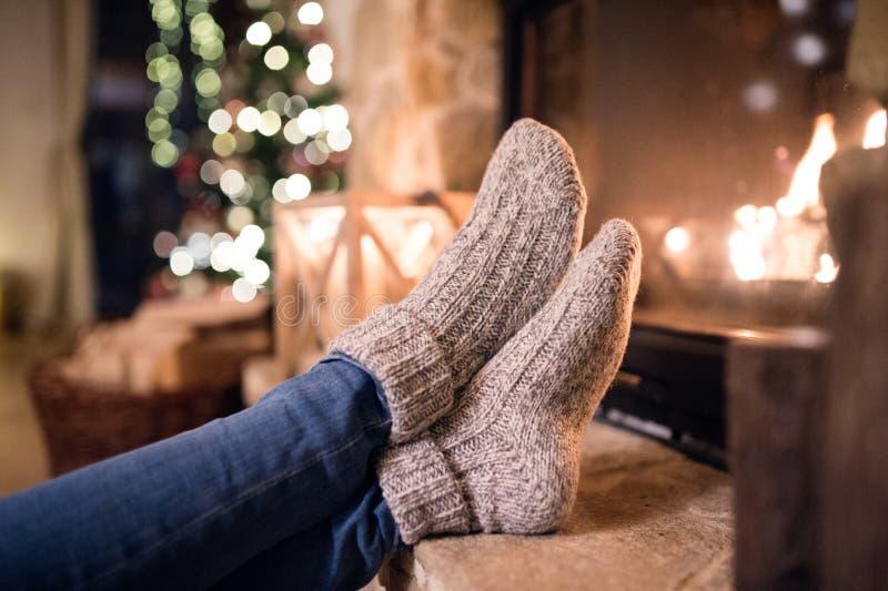 Pies de la mujer irreconocible en calcetines por la chimenea de la Navidad imágenes de archivo libres de regalías