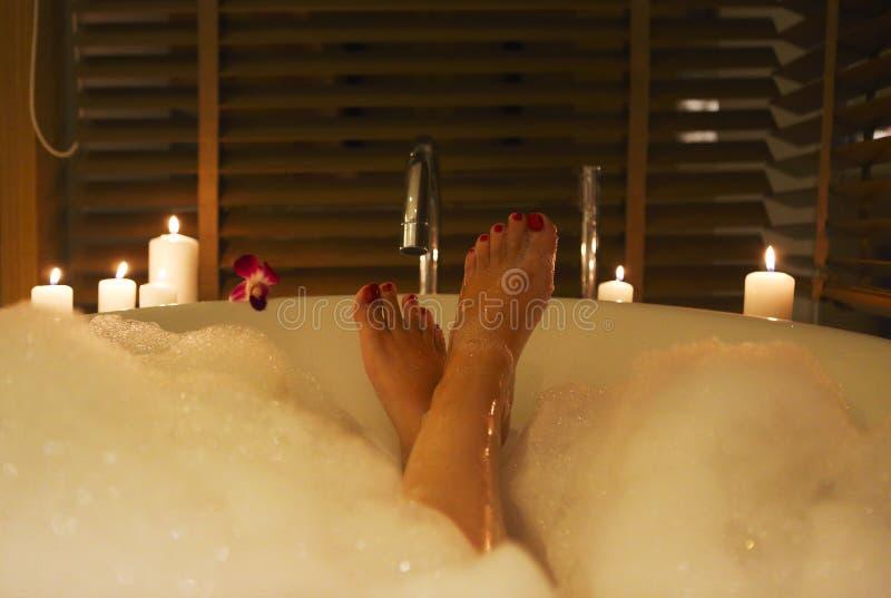 Pies de la mujer joven en baño con espuma y velas fotos de archivo libres de regalías