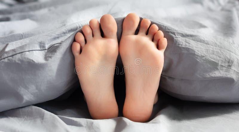 Pies de la mujer joven que mienten en cama foto de archivo