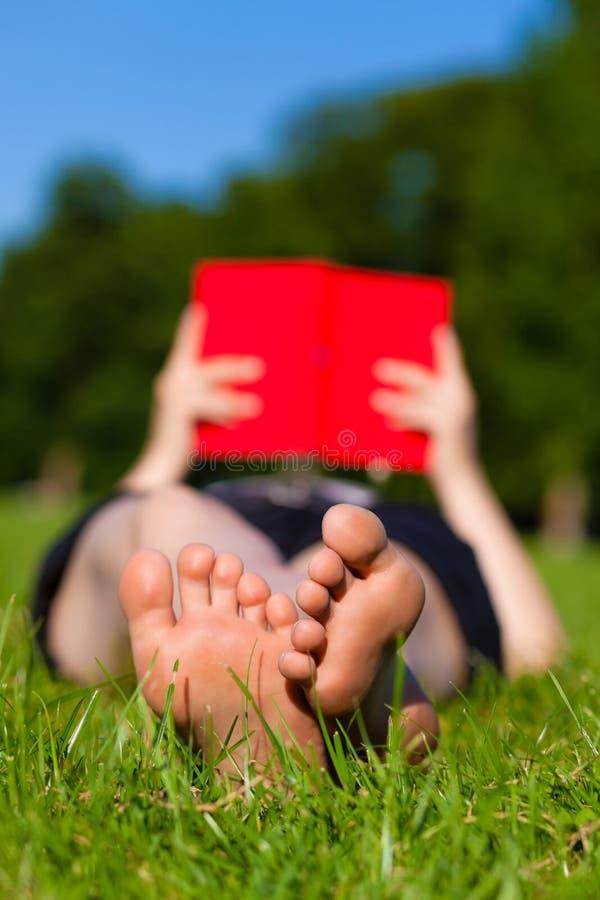 Pies de la mujer mientras que lee un libro foto de archivo