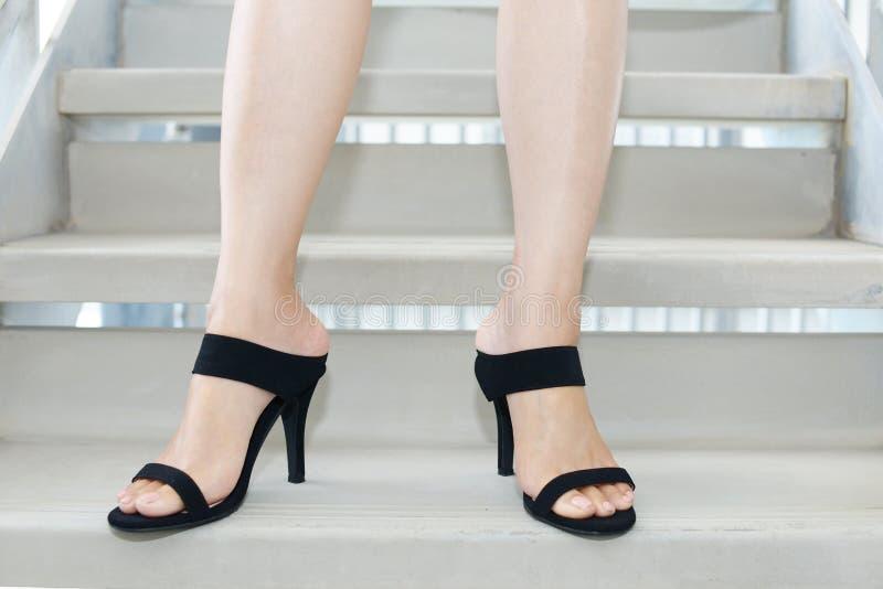 Pies de la mujer que llevan las sandalias negras del talón foto de archivo libre de regalías