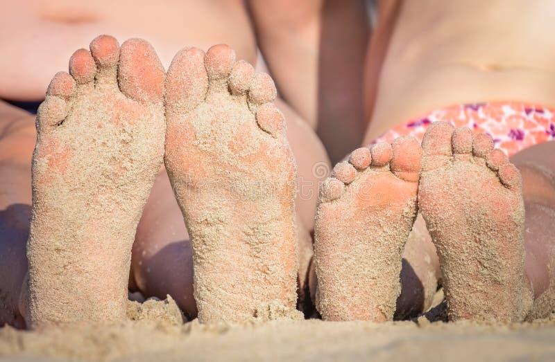 Pies de las muchachas en la playa fotografía de archivo libre de regalías