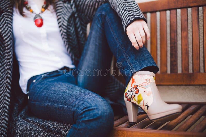 Pies de las muchachas en las botas de cuero beige con bordado en un banco de madera imagen de archivo