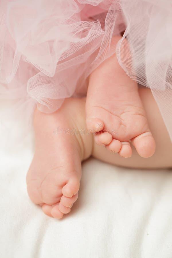Pies de los bebés con el vestido de Tulle en blanco imagen de archivo libre de regalías