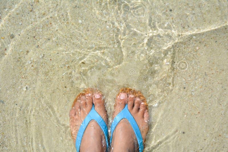 pies de mujeres y sandalia en la playa imagenes de archivo