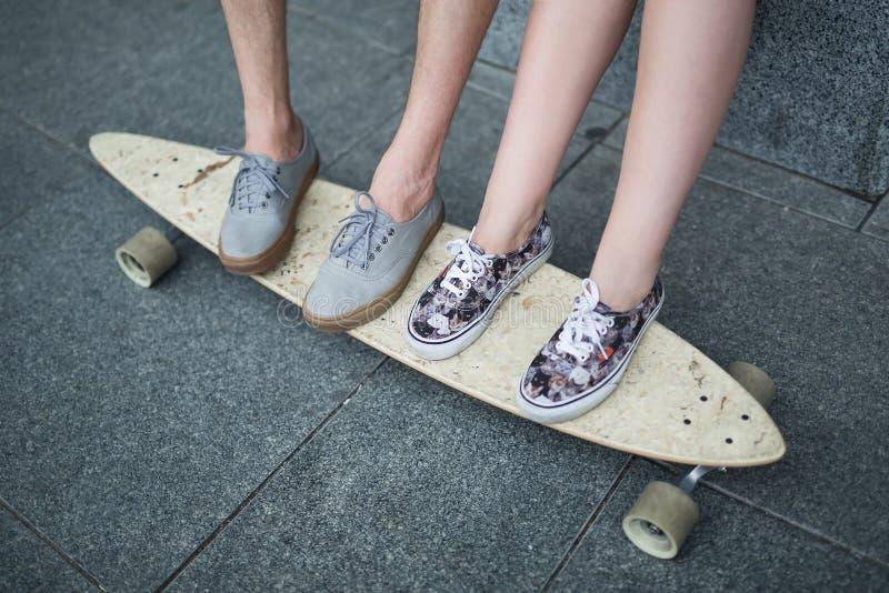Pies de pares de adolescentes en el primer del longboard fotos de archivo libres de regalías
