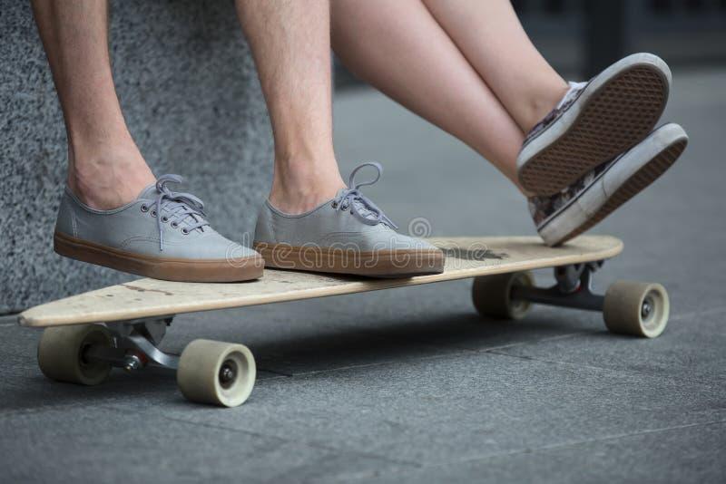 Pies de pares de adolescentes en el primer del longboard foto de archivo