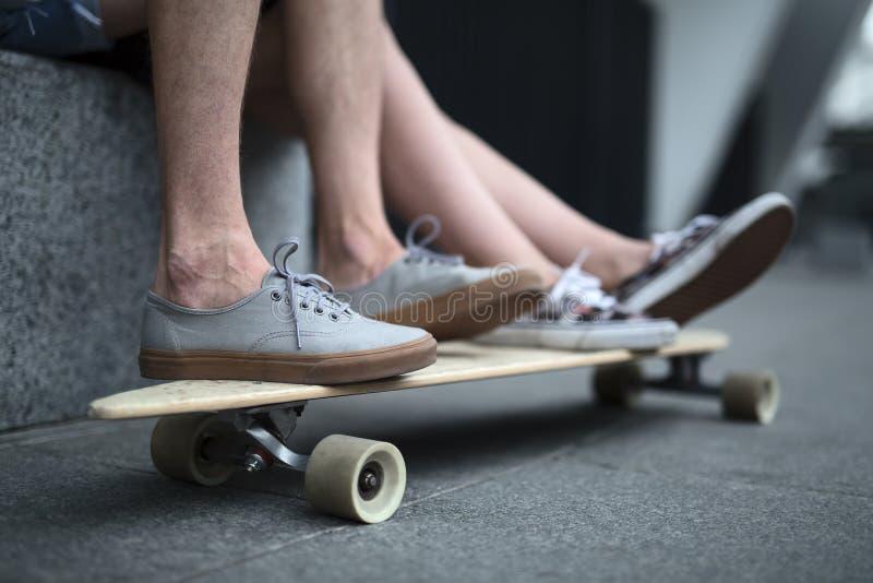 Pies de pares de adolescentes en el primer del longboard fotografía de archivo libre de regalías