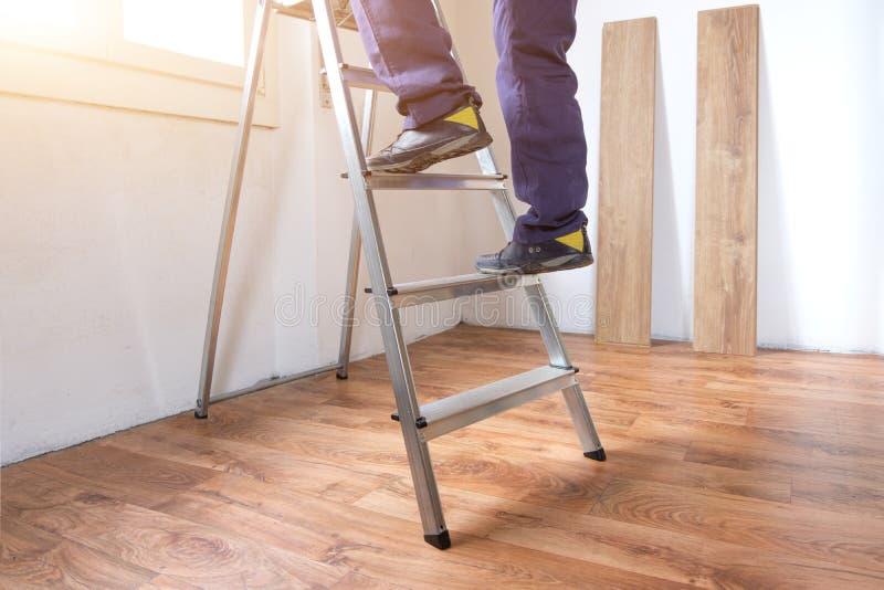 Pies de un carpintero listo para el trabajo sobre una escalera fotos de archivo libres de regalías