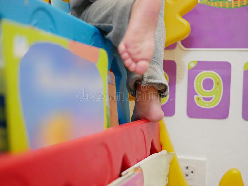 Pies de un pequeño bebé que sube y que camina en los estantes de librería imágenes de archivo libres de regalías