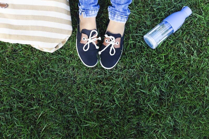 Pies de una chica joven en un fondo una hierba verde con la botella o fotografía de archivo