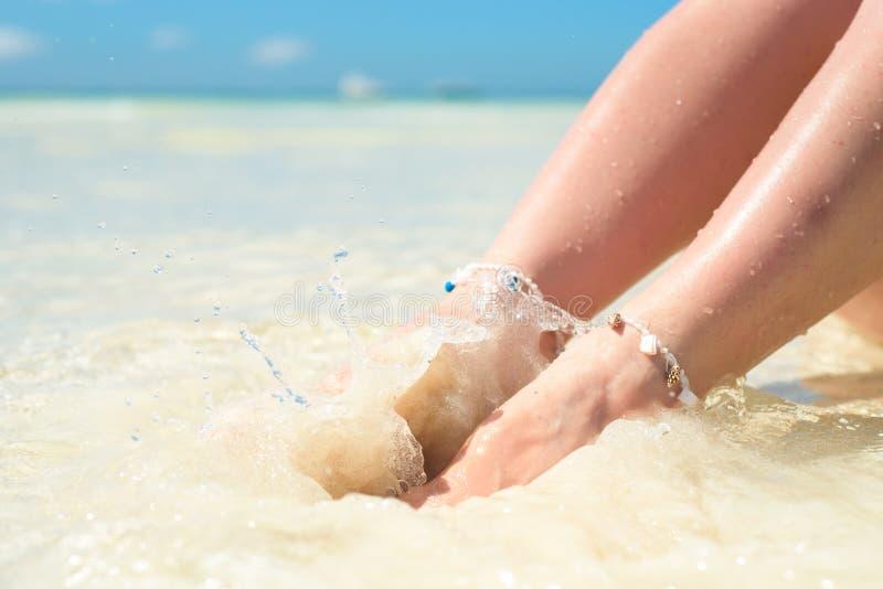Pies de una mujer en el espray de la agua de mar limpia imagen de archivo libre de regalías