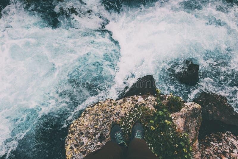 Pies de viajero que se coloca en piedra en la aventura del concepto de la forma de vida del viaje de agua de río fotografía de archivo libre de regalías