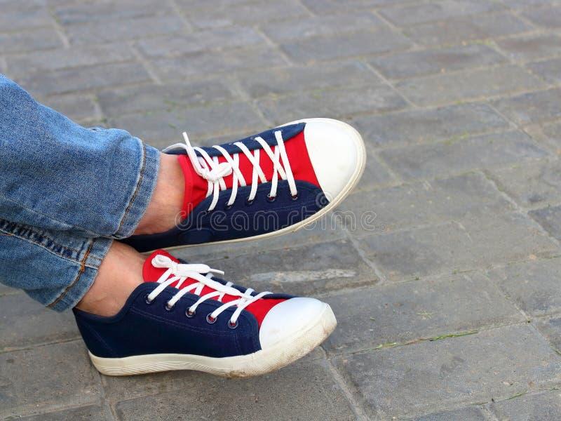 Pies de zapatillas de deporte en el parque encendido fotos de archivo