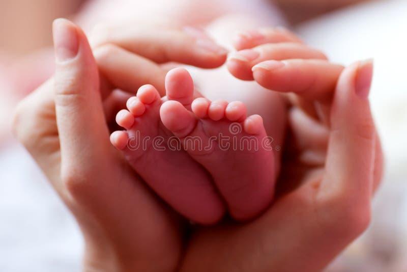 Pies del bebé ahuecados en las manos de las madres imagenes de archivo