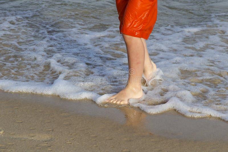 Pies del niño en la playa fotos de archivo