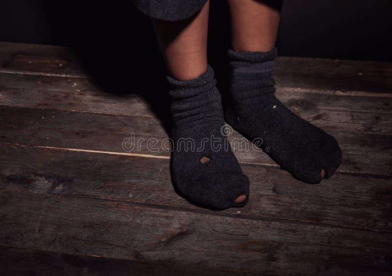 Pies del niño pequeño en calcetines permeables imagenes de archivo